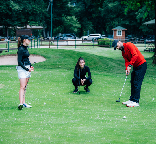 golf coach teach this young girl to roll the ball